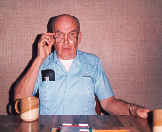 Bill Logan holding his glasses while seated at a bridge table